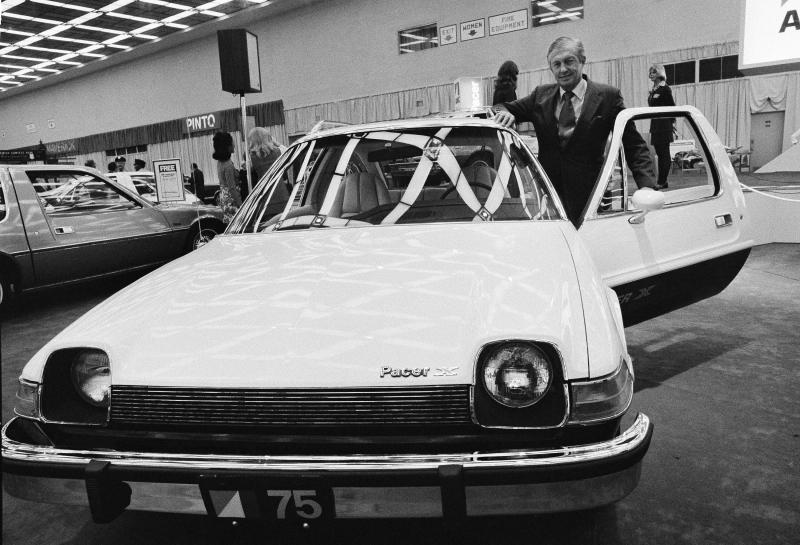 FILE - In this Jan. 12, 1975, file photo, American Motors' board chairman Roy D. Chapin checks over the company's new sub-compact Pacer during a preview ceremony at the 1975 Detroit Auto Show. Show organizers expect more than 50 new model introductions when the 2014 show kicks off Monday Jan. 13, 2014. (AP Photo/File)
