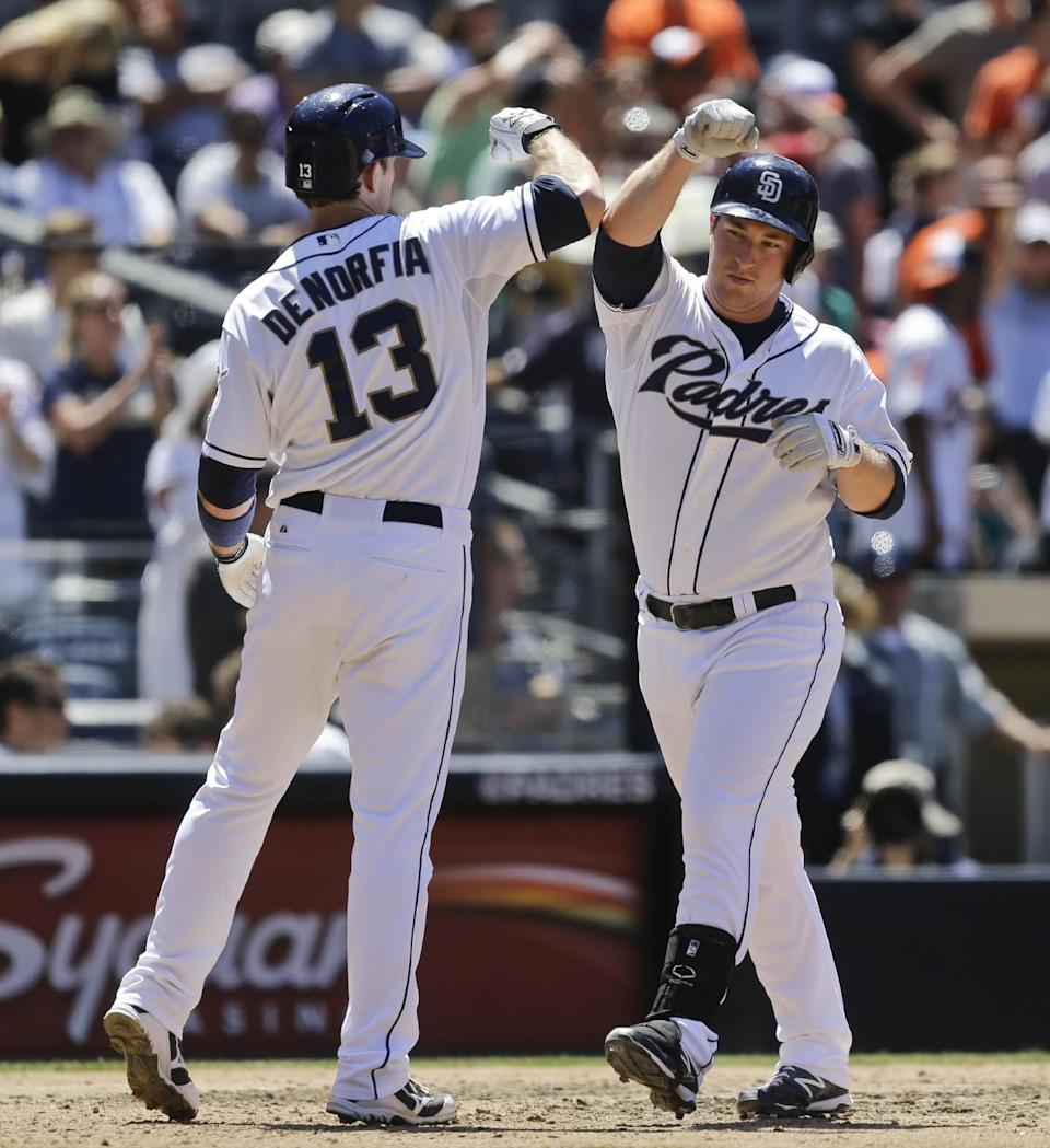 San Diego Padres' Jedd Gyorko bangs forearms with Chris Denorfia after hitting a three-run home run against the Baltimore Orioles in the sixth inning of a baseball game in San Diego, Wednesday, Aug. 7, 2013. (AP Photo/Lenny Ignelzi)
