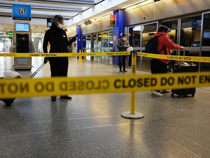 Three people with suitcases spread apart in an airport behind yellow caution tape.