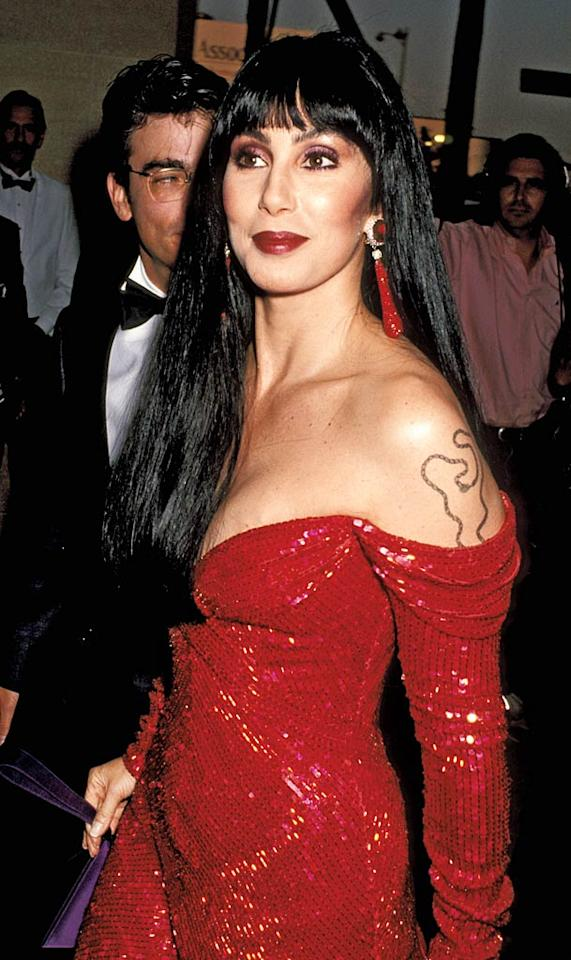 """<b>1991:</b> Cher did a cameo in Robert Altman's """"The Player"""" wearing a bugle-beaded gown from Bob Mackie's runway show. """"This is one of the rare times I wore red lipstick. But it matched the dress! That tattoo was newish -- a chain with crosses, hearts and ankhs -- no one knew what it was but me.""""   <a href=""""http://www.instyle.com/instyle/package/general/photos/0,,20396039_20436052_20866423,00.html?xid=omg-cher-sexy-jeans?yahoo=yes"""" target=""""new"""">InStyle Picks the Sexiest Jeans Ever</a> Jim Smeal/<a href=""""http://www.wireimage.com"""" target=""""new"""">WireImage.com</a> - 1991 :"""