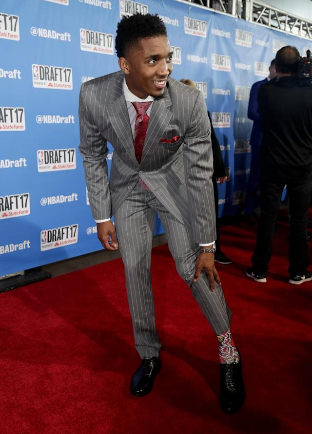 <p>Louisville's Donovan Mitchell shows off his socks while stopping for photos on the red carpet before the start of the NBA basketball draft, Thursday, June 22, 2017, in New York. (AP Photo/Frank Franklin II) </p>