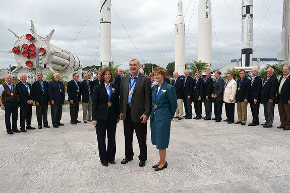 The 2013 class of U.S. Astronaut Hall of Fame inductees, Bonnie Dunbar (left), Curt Brown and Eileen Collins, are flanked by two dozen of their fellow Hall of Fame astronauts at the Kennedy Space Center Visitor Complex in Florida, April 20, 201