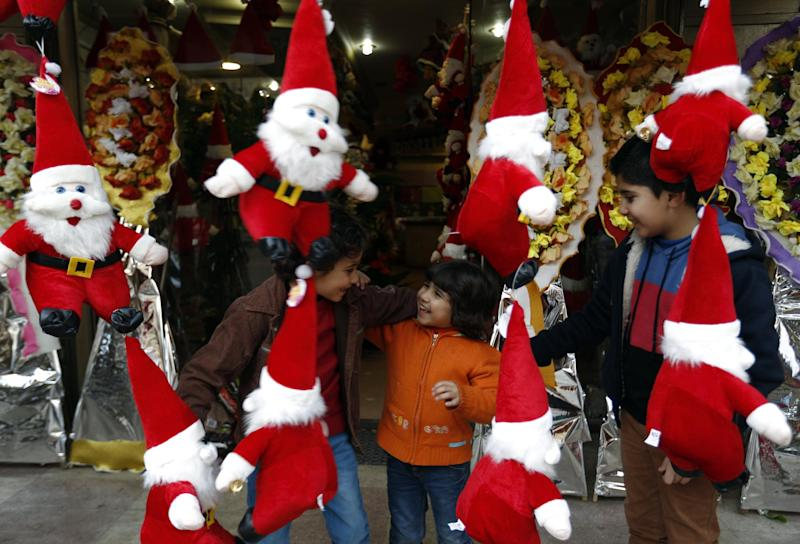 Palestinian children play next to a stand selling toys in Gaza City on December 24, 2014 (AFP Photo/Mohammed Abed)