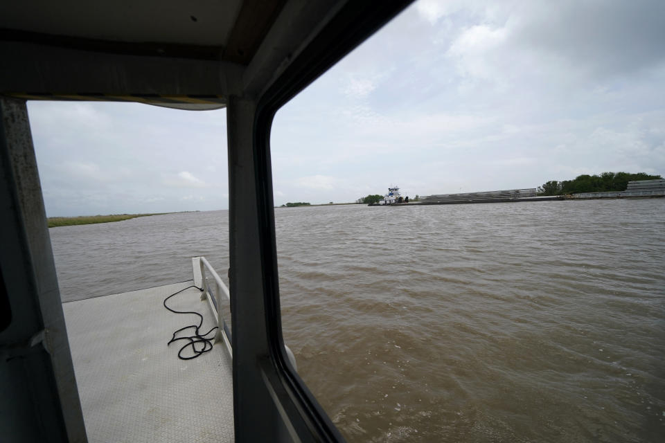 """A tugboat pushes barges along the Intracoastal Waterway, which has encroached on marshland over the years, on Avery Island, La., where Tabasco brand pepper sauce is made, Tuesday, April 27, 2021. As storms grow more violent and Louisiana loses more of its coast, the family that makes Tabasco Sauce is fighting erosion in the marshland that buffers its factory from hurricanes and floods. Overall, it's probably a standoff, says CEO and president Harold """"Took"""" Osborn, great-great-grandson of the McIlhenny Co.'s founder. (AP Photo/Gerald Herbert)"""