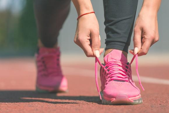 Female sport fitness runner tying her pink sneakers' shoelaces and getting ready for jogging outdoors on running track.
