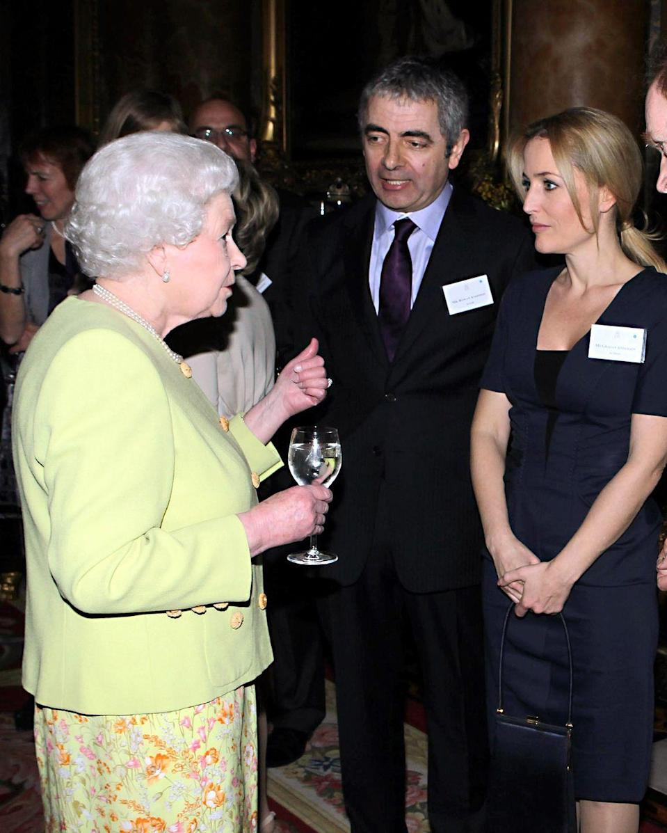 <p>Gillian Anderson wore a structured navy sheath dress to a reception at Buckingham Palace to meet Queen Elizabeth. Who knew the actress would play England's former prime minister Margaret Thatcher nearly a decade later on <em>The Crown</em>?</p>