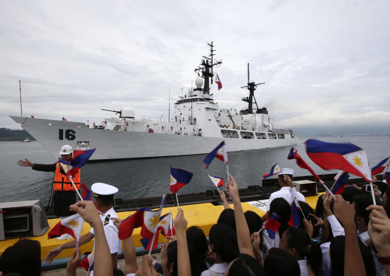 Students and other guests wave Philippine flags to welcome the second warship of the Philippine Navy, the BRP Ramon Alcaraz Tuesday, Aug. 6, 2013 at Subic Freeport, about 80 kilometers (50 miles) northwest of Manila, Philippines. The Philippines on Tuesday celebrated the arrival of its second major warship to challenge China's massive territorial claims in the South China Sea that Filipino officials say have intruded into their country's potentially oil-rich offshore territory. (AP Photo/Bullit Marquez)