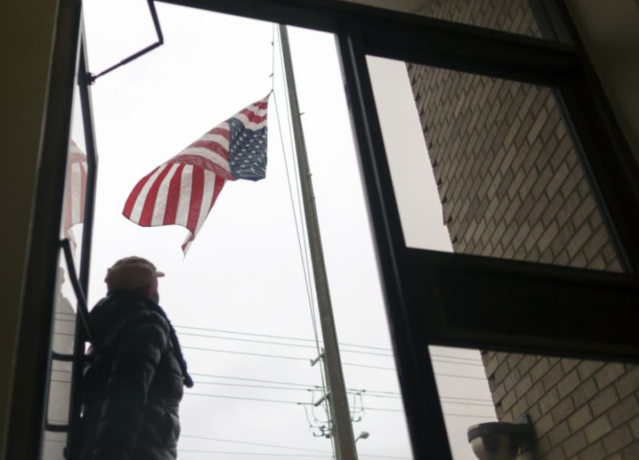 A US Postal worker takes down a frozen American flag after the top hook that attached it to the pole broke, Wednesday, Jan. 3, 2018, in Savannah, Ga. (AP Photo/Stephen B. Morton)