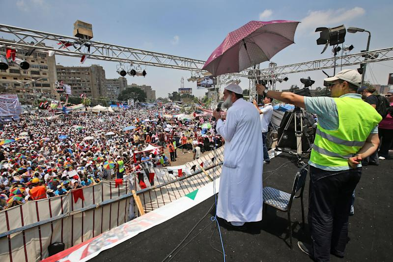 "A supporter of Egypt's ousted President Mohammed Morsi holds an umbrella over the head of a cleric delivering the Friday prayer sermon, where protesters have installed their camp and hold their daily rally, at Nasr City, Cairo, Egypt, Friday, July 19, 2013. Thousands of protesters are holding rallies across Egypt to demand the reinstatement of ousted President Mohammed Morsi. The Muslim Brotherhood, from which Morsi hails, is mobilizing followers to march in Cairo and elsewhere Friday for a protest they're dubbing ""Breaking the Coup."" (AP Photo/Hussein Malla)"