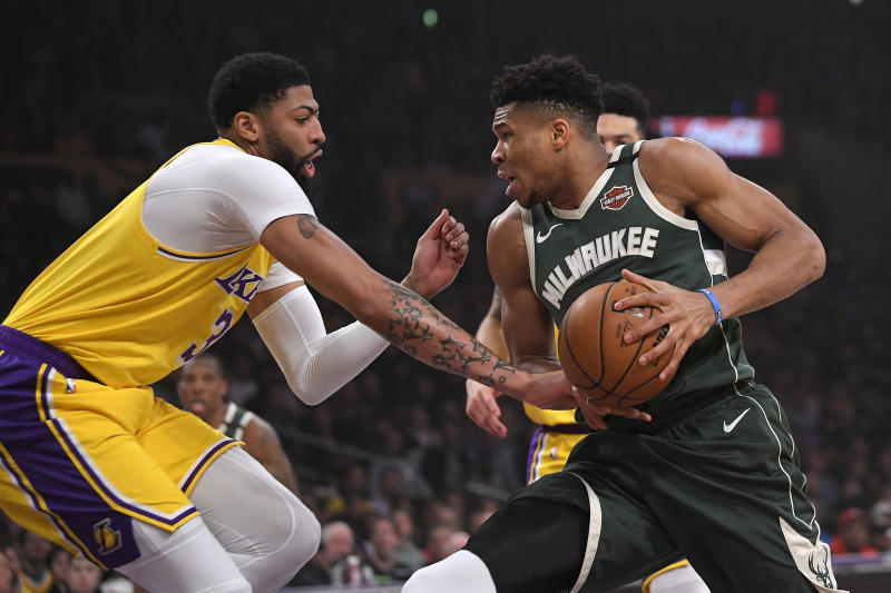 Milwaukee Bucks forward Giannis Antetokounmpo, right, drives to the basket as Los Angeles Lakers forward Anthony Davis defends during the first half of an NBA basketball game Friday, March 6, 2020, in Los Angeles. (AP Photo/Mark J. Terrill)