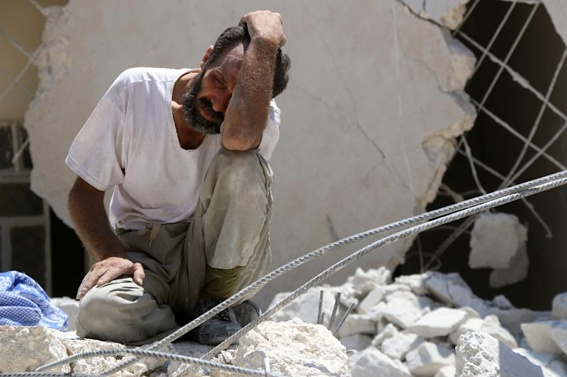 A man waits as Syrian civil defence workers look for survivors under the rubble of a collapsed building following reported air strikes on July 17, 2016 in Aleppo (AFP Photo/Thaer Mohammed)