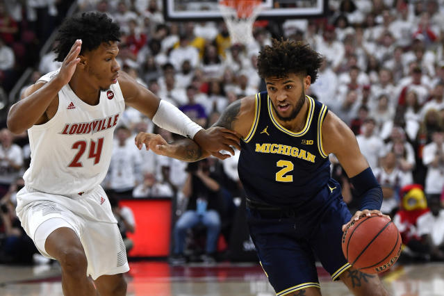 Michigan forward Isaiah Livers (2) attempts to get around the defense of Louisville forward Dwayne Sutton (24) during the first half of an NCAA college basketball game in Louisville, Ky., Tuesday, Dec. 3, 2019. (AP Photo/Timothy D. Easley)