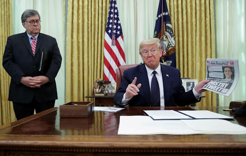 U.S. President Donald Trump speaks to reporters about an executive order regarding social media companies as Attorney General Bill Barr listens in the Oval Office of the White House in Washington, U.S., May 28, 2020. REUTERS/Jonathan Ernst TPX IMAGES OF THE DAY