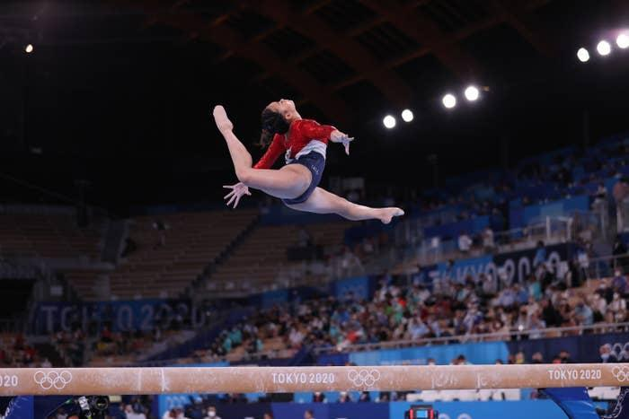A gymnast in a full split high over the balance beam