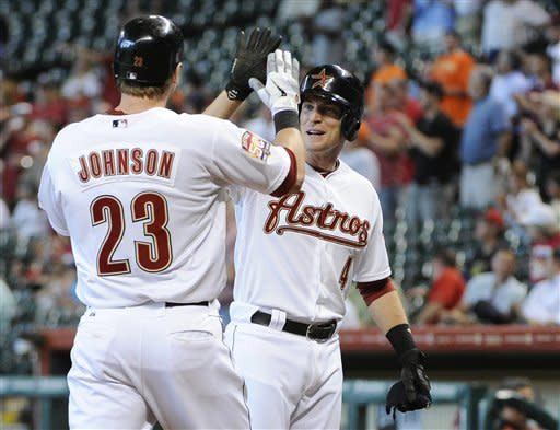 Houston Astros' Jed Lowrie (4) welcomes teammate Chris Johnson (23) at home plate after Johnson hit a three-run home run against the New York Mets in the second inning of a baseball game, Wednesday, May 2, 2012, in Houston. (AP Photo/Pat Sullivan)