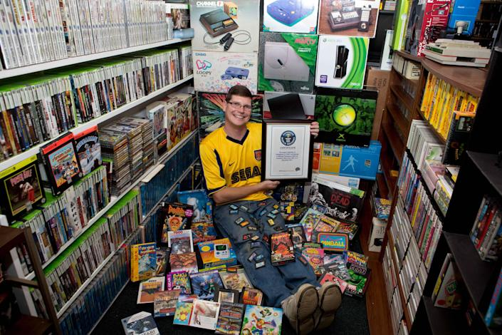 """In this Sept. 1, 2013 photo provided by Brianna Blank, Michael Thomasson poses in the basement of his suburban Buffalo home, where he stores his collection of video games. Thomasson is featured in the just-released """"Guinness World Records 2014 Gamer's Edition,"""" for having the largest collection of video games, 10,607. The number bests the previous record holder, Richard Lecce of Florida, who had 8,616 games in 2010. (AP Photo/Brianna Blank)"""