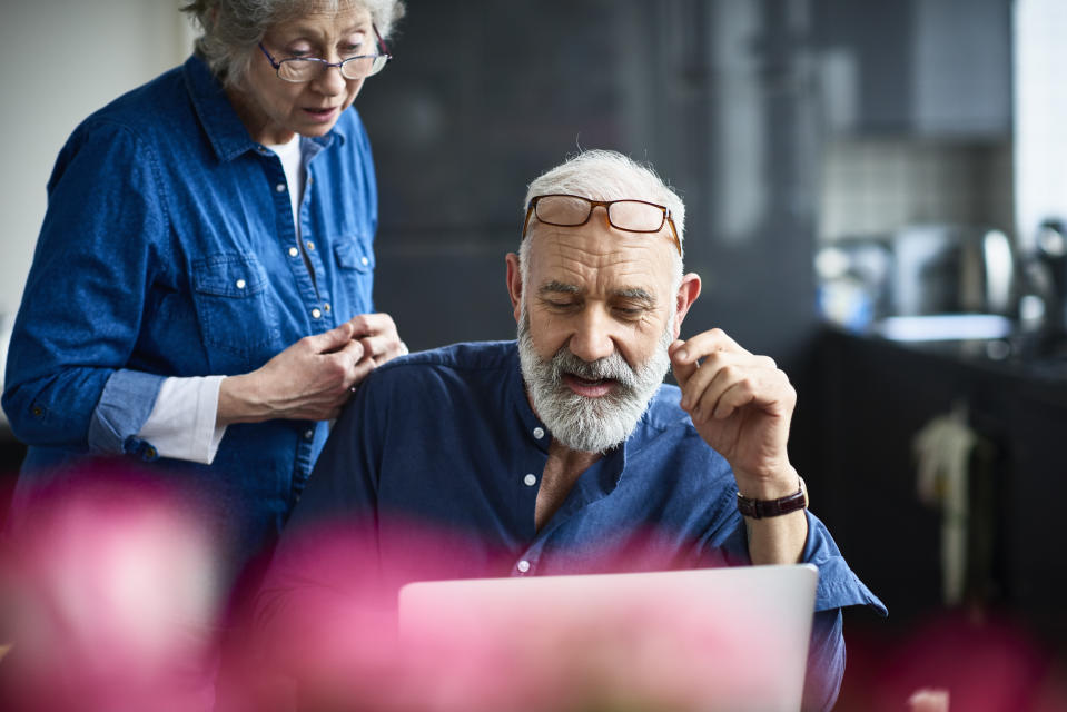 Candid portrait of senior couple at home, man with grey hair and beard working on computer, glasses resting on forehead, seniorpreneur working from home with wife