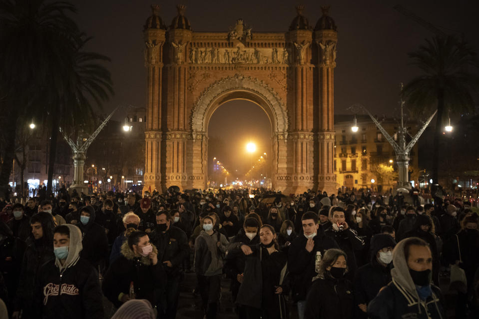 Demonstrators march near the Arch of Triumph during a protest condemning the arrest of rap artist Pablo Hasél in Barcelona, Spain, Monday, Feb. 22, 2021. Pablo Hasel spent 24 hours barricaded in a university building before police took him away last week to serve a 9-month prison sentence for insulting the Spanish monarchy and praising terrorist violence in his music. (AP Photo/Felipe Dana)