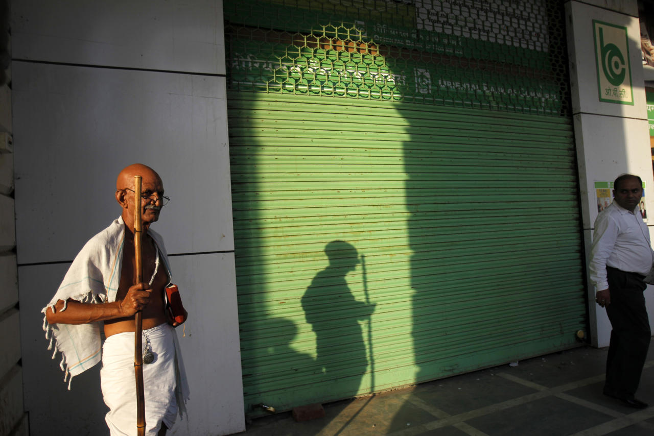 Mahesh Chaturvedi (L), 63, who dresses up like Mahatma Gandhi, stands outside a closed shop in New Delhi September 28, 2012. Chaturvedi says that the soul of Gandhi resides in him and he has been sent to continue the work of Father of the Nation. After his self proclaimed transformation in 2002 as Gandhi, Chaturvedi has been travelling extensively and plays up to his startling resemblance to Gandhi at protests and demonstrations. Picture taken September 28, 2012. REUTERS/Mansi Thapliyal   (INDIA - Tags: SOCIETY)
