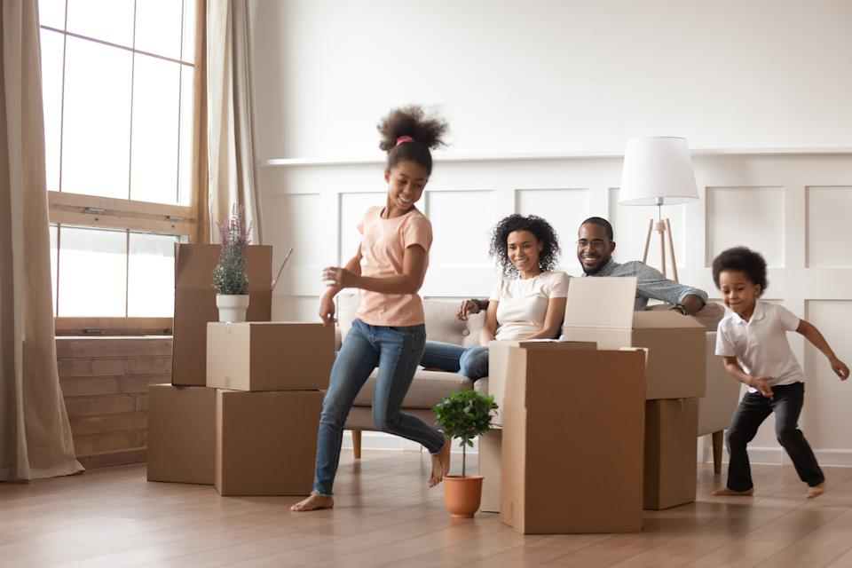 Active funny kids play run around cardboard boxes having fun on moving day with black parents sit on sofa, happy african american family children mom dad laughing in living room celebrate relocation