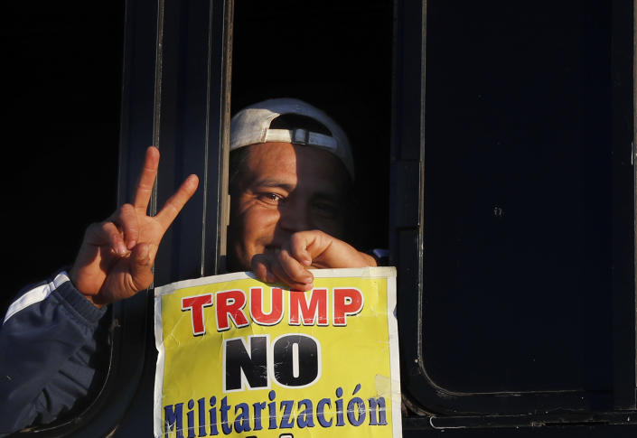 """<p>A migrant traveling with a caravan hoping to reach the U.S. border, holds a sign with a message that reads in Spanish: """"Trump, No to militarization of the border,"""" after boarding a bus in La Concha, Mexico, Wednesday, Nov. 14, 2018. (Photo: Marco Ugarte/AP) </p>"""