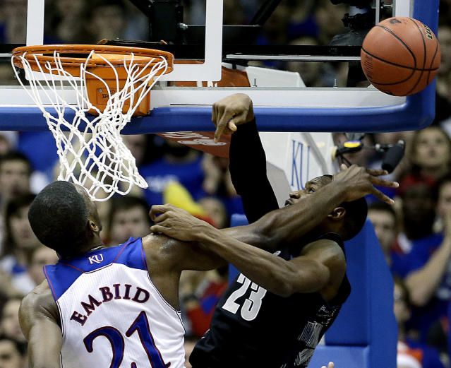 Kansas' Joel Embiid (21) blocks a shot by Georgetown's Aaron Bowen (23) during the first half of an NCAA college basketball game Saturday, Dec. 21, 2013, in Lawrence, Kan. (AP Photo/Charlie Riedel)