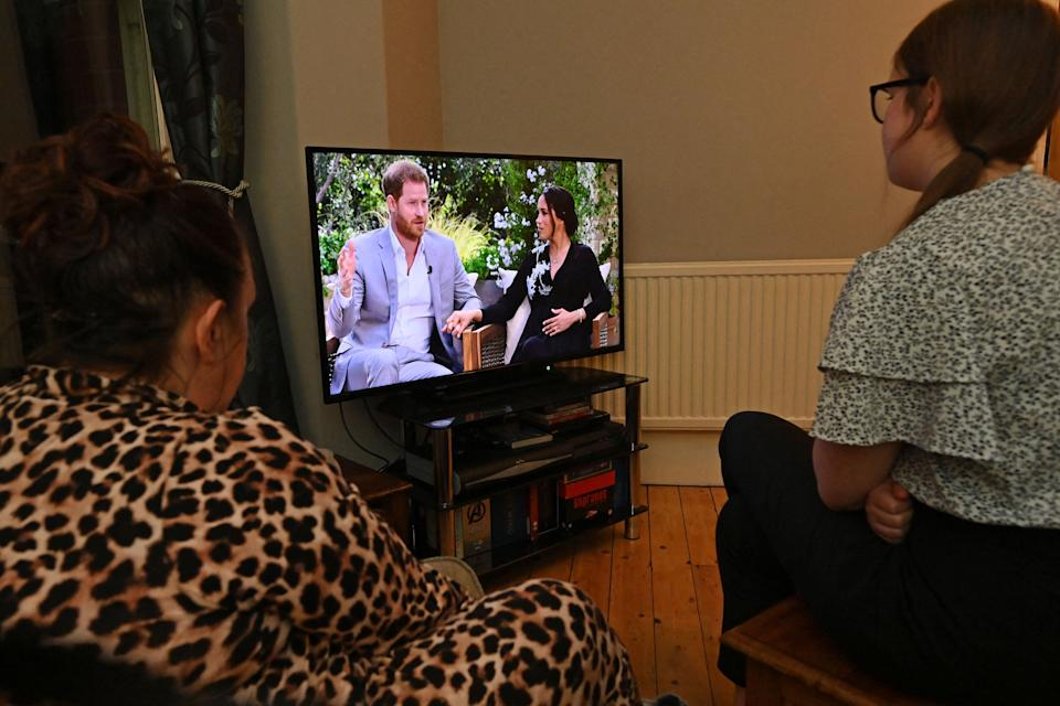 A family gather around the television in Liverpool, north west England to watch Prince Harry and his wife Meghan's explosive tell-all interview on CBS with Oprah Winfrey, on March 8, 2021, as national television in Britain shows the interview a day later then in the US. - Suicidal thoughts, a racist relative and an heir-to-the-throne trapped by tradition -- Prince Harry and his wife Meghan have lifted the lid on life inside Britain's royal family with an explosive interview that reverberated around the world. (Photo by Paul ELLIS / AFP) (Photo by PAUL ELLIS/AFP via Getty Images)