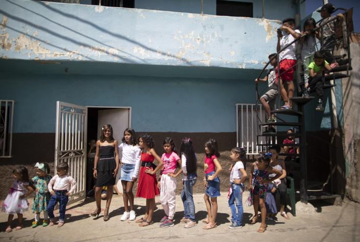 Contestants between the ages of 3 and 12 compete in a homespun beauty pageant in the Antimano neighborhood of Caracas, Venezuela, Friday, Feb. 5, 2021. Neighbors in the hillside barrio gathered for the carnival pageant tradition to select their child queen for the upcoming festivities. (AP Photo/Ariana Cubillos)