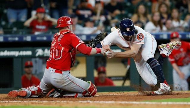Houston's Jake Marisnick, right, was suspended for two games Thursday by Major League Baseball for colliding with Los Angeles Angels catcher Jonathan Lucroy, left, at home plate in a game Sunday (AFP Photo/Bob Levey)