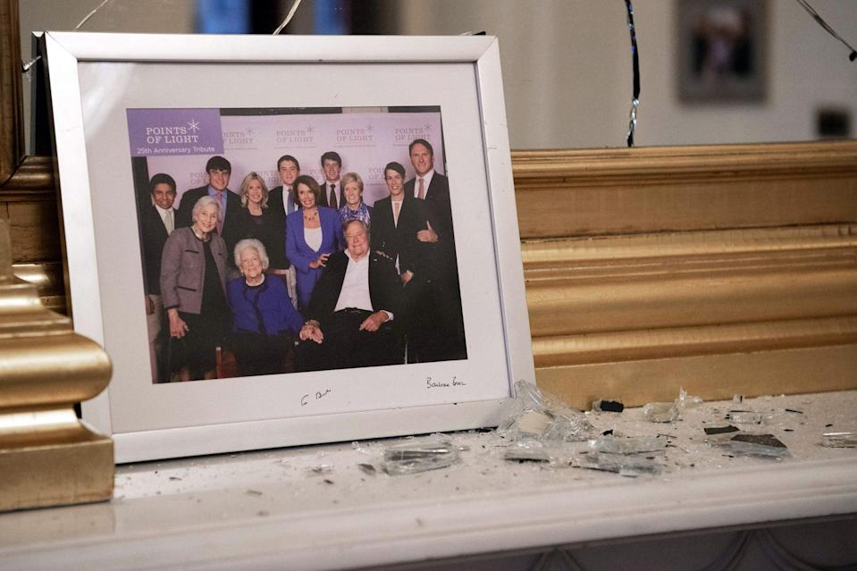 <p>A photo of Speaker of the House Nancy Pelosi with former President of the United States George H.W. Bush, and his wife, Barbara Bush, was left broken on the mantel of her office. </p>