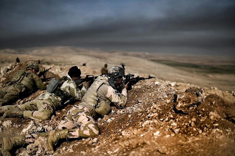 Members of the Iraqi army's 9th Division hold a position on a hill in Talul al-Atshana, on the southwestern outskirts of Mosul, on February 27, 2017, during an offensive to retake the city from Islamic State group fighters