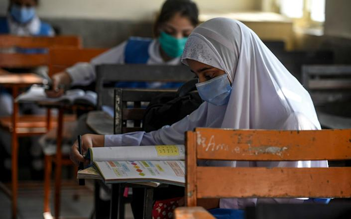 Children wearing facemasks attend a class at a school in Islamabad on September 30, 2020, after the educational institutes reopened primary classes in the third and last phase nearly six months after the spread of the Covid-19 coronavirus. - Aamir Qureshi/AFP