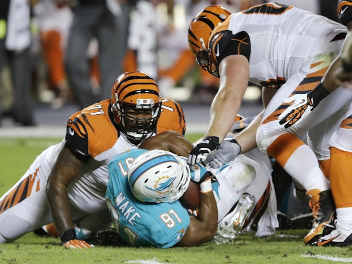 Miami Dolphins defensive end Cameron Wake (91) recovers a fumble by Cincinnati Bengals quarterback Andy Dalton, between Bengals tackle Andre Smith (71) and guard Kevin Zeitler (68) during the first half of an NFL football game, Thursday, Oct. 31, 2013, in Miami Gardens, Fla. (AP Photo/Wilfredo Lee)