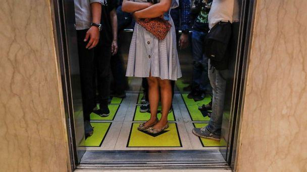 PHOTO: Workers stand on social distancing marks inside an elevator of the Senayan City shopping mall in Jakarta, Indonesia, June 9, 2020. (Mast Irham/EPA/Rex via Shutterstock)