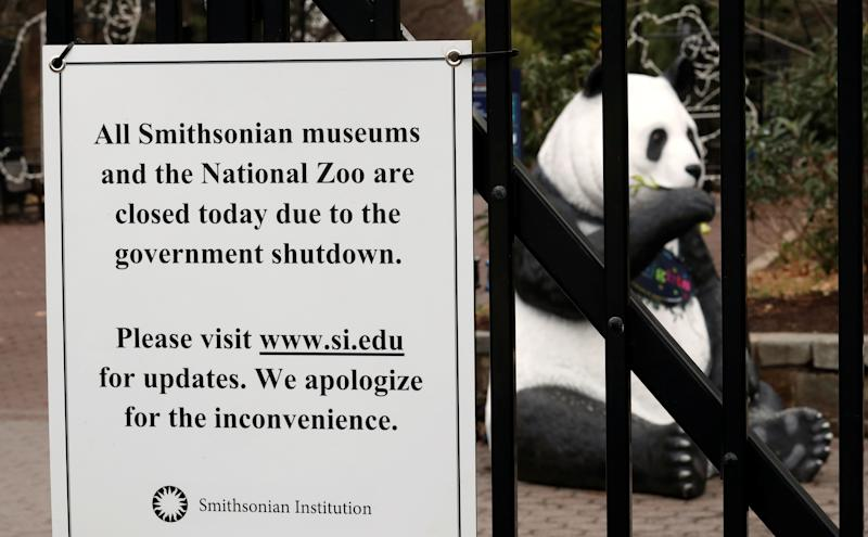 The figure of a panda is seen behind a sign telling the public that the National Zoo is closed due to the partial government shutdown in Washington, U.S., January 2, 2019. REUTERS/Kevin Lamarque - RC182C8B77D0