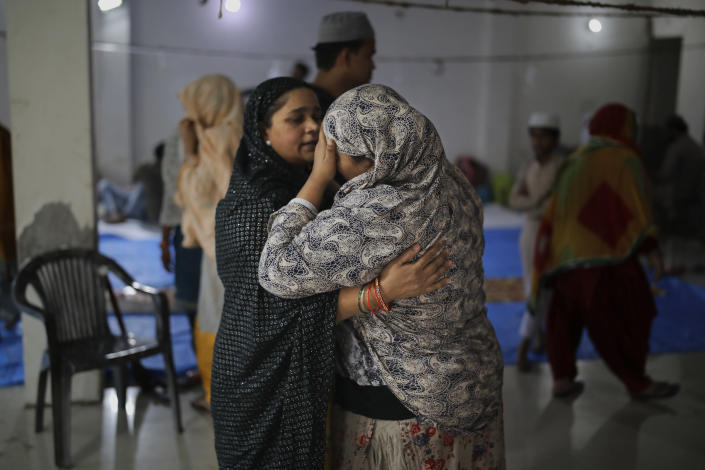 In this Friday, Feb. 28, 2020 photo, a woman comforts a neighbor inside a hall at Al-Hind hospital used as a shelter for people who were rescued after they were attacked by a Hindu mob, in Old Mustafabad neighborhood of New Delhi, India. On the eve of U.S. President Donald Trump's first state visit to India last Sunday, Hindus and Muslims in the Indian capital charged at each other with homemade guns and crude weapons, leaving the streets where the rioting occurred resembling a war zone, with houses, shops, mosques, schools and vehicles up in flames, more than 40 dead and hundreds injured. (AP Photo/Altaf Qadri)