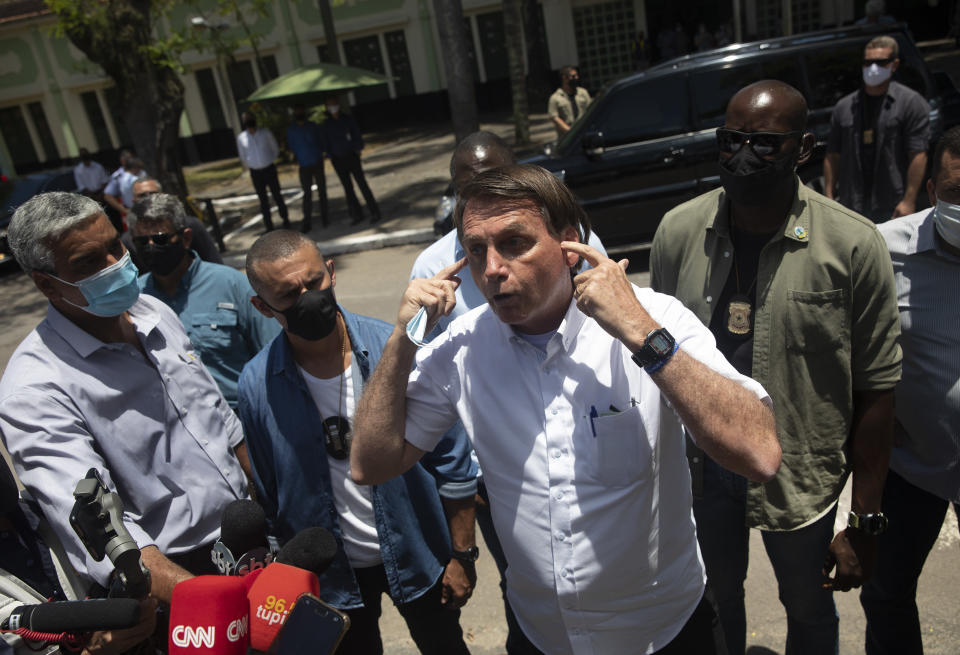 "Brazil's President Jair Bolsonaro talks with the media outside a polling station, after voting during the run-off municipal elections in Rio de Janeiro, Brazil, Sunday, Nov. 29, 2020. Bolsonaro, who sometimes has embraced the label ""Trump of the Tropics,"" said Sunday he'll wait a little longer before recognizing the U.S. election victory of Joe Biden, while also echoing President Donald Trump's allegations of irregularities in the U.S. vote. (AP Photo/Silvia Izquierdo)"