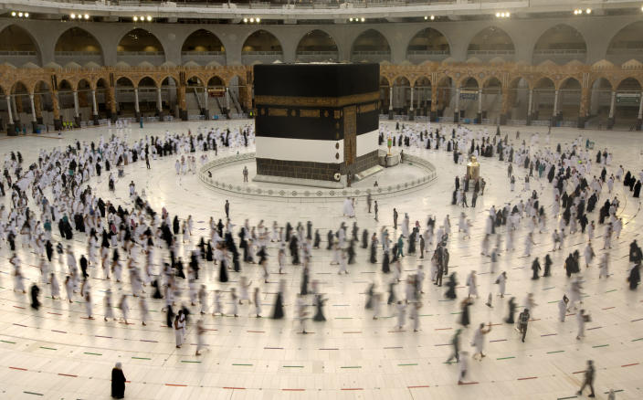 In this photo taken with low shutter speed, Muslim pilgrims circumambulate the Kaaba, the cubic building at the Grand Mosque, as they wear masks and keep social distancing, a day before the annual hajj pilgrimage, Saturday, July 17, 2021. The pilgrimage to Mecca required once in a lifetime of every Muslim who can afford it and is physically able to make it, used to draw more than 2 million people. But for a second straight year it has been curtailed due to the coronavirus with only vaccinated people in Saudi Arabia able to participate. (AP Photo/Amr Nabil)