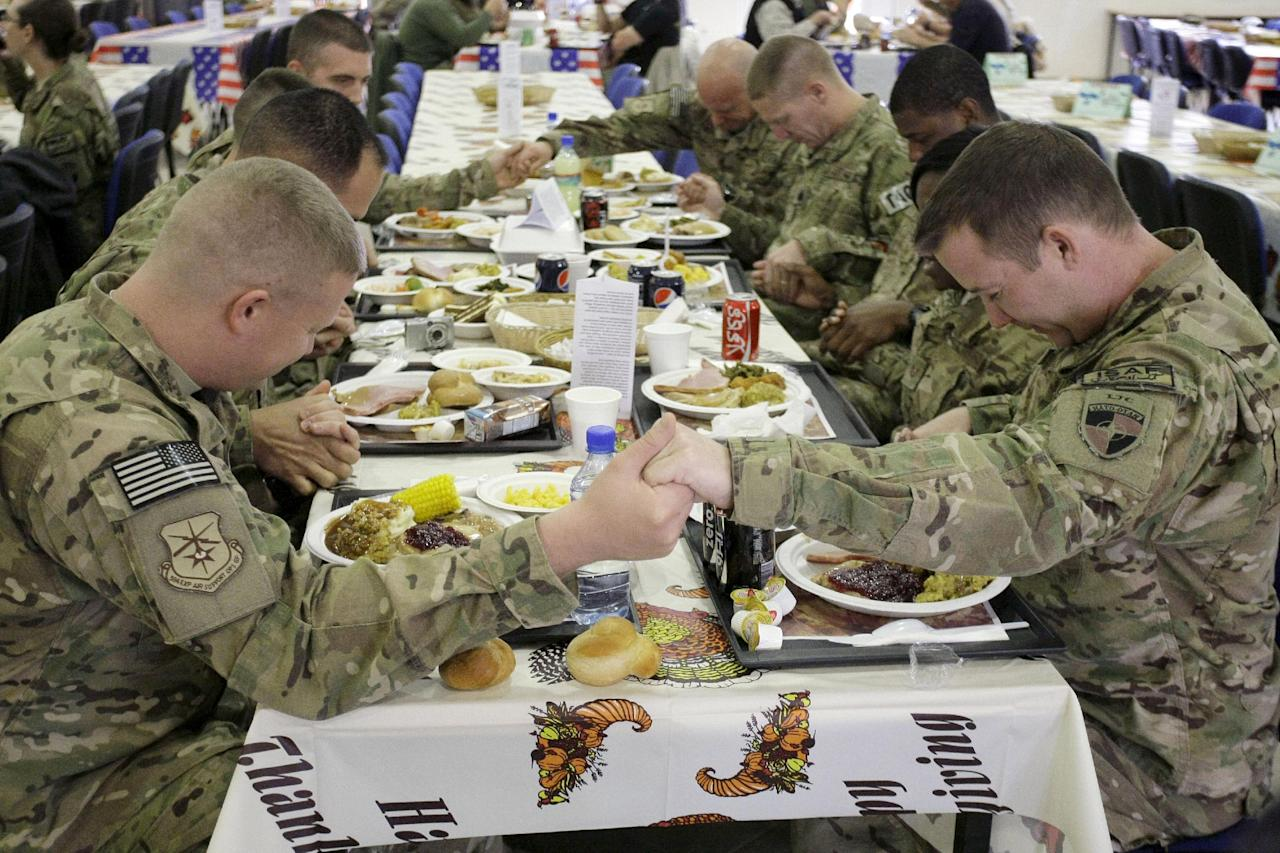 U.S. soldiers pray before eating a Thanksgiving meal at a dining hall at the U.S.-led coalition base in Kabul, Afghanistan, Thursday, Nov. 22, 2012. The dining hall at the U.S.-led coalition base in the Afghan capital served up mac-and-cheese along with traditional Thanksgiving Day fixings. (AP Photo/Musadeq Sadeq)