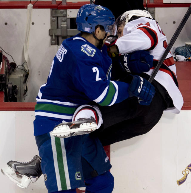 Vancouver Canucks defenseman Dan Hamhuis (2) puts New Jersey Devils center Andrei Loktionov into the boards during the second period of an NHL hockey game Tuesday, Oct. 8, 2013, in Vancouver, British Columbia. (AP Photo/The Canadian Press, Jonathan Hayward)