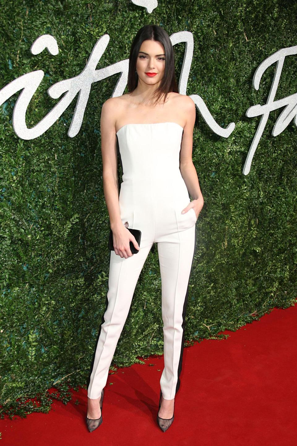 Kendall Jenner, wearing a cream jumpsuit, supported her friend Cara Delevingne.