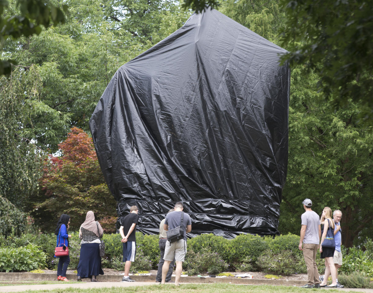 <p>Residents and visitors look over the covered Ce statue of Confederate General Robert E. Lee in Emancipation park in Charlottesville, Va., Wednesday, Aug. 23, 2017. (Photo: Steve Helber/AP) </p>