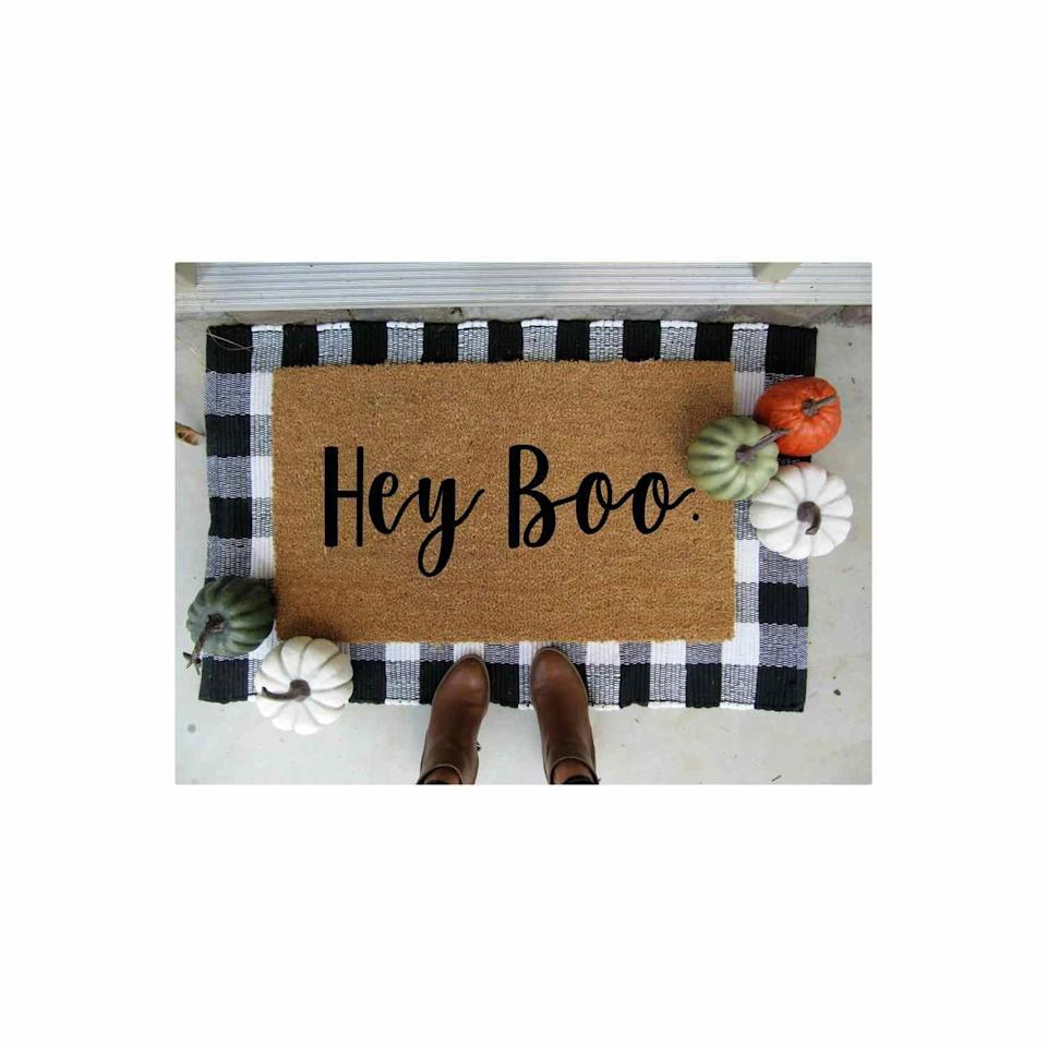 """<p><strong>CindyHughesDesign</strong></p><p>etsy.com</p><p><strong>$45.00</strong></p><p><a href=""""https://go.redirectingat.com?id=74968X1596630&url=https%3A%2F%2Fwww.etsy.com%2Flisting%2F709444720%2Fhey-boo-doormat-customized-doormat&sref=https%3A%2F%2Fwww.oprahmag.com%2Flife%2Fg33335421%2Ffall-porch-decor-ideas%2F"""" rel=""""nofollow noopener"""" target=""""_blank"""" data-ylk=""""slk:SHOP NOW"""" class=""""link rapid-noclick-resp"""">SHOP NOW</a></p><p>Welcome visitors with a punny door mat. Bonus style points for layering it with a larger plaid outdoor rug. </p>"""