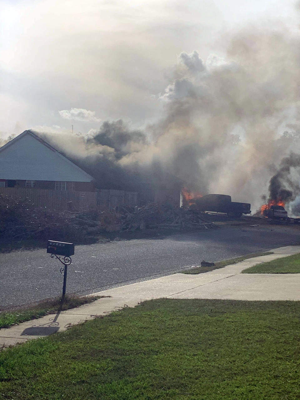 Cars and a house seen in flames as smoke rises in a residential neighbourhood after a US Navy training plane crashed in Alabama.