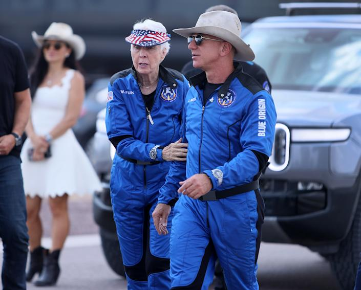 VAN HORN, TEXAS - JULY 20: Blue Origin's New Shepard crew (L-R) Wally Funk and Jeff Bezos walk together after flying into space in the rocket on July 20, 2021 in Van Horn, Texas. Mr. Bezos and the crew were the first human spaceflight for the company.   (Photo by Joe Raedle/Getty Images)