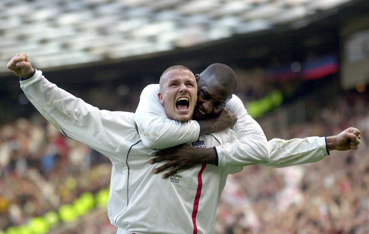 "FILE - This is a Saturday, Oct. 6, 2001 file photo of England's captain David Beckham, left, as he  is congratulated by teammate Emile Heskey after scoring their second goal against Greece during their 2002 World Cup qualifying match at Old Trafford Manchester England. David Beckham is retiring from soccer after the season, ending a career in which he become a global superstar since starting his career at Manchester United. The 38-year-old Englishman recently won a league title in a fourth country with Paris Saint-Germain. He said in a statement Thursday May 16, 2013 he is ""thankful to PSG for giving me the opportunity to continue but I feel now is the right time to finish my career, playing at the highest level.""  (AP Photo/Adam Butler, File)"