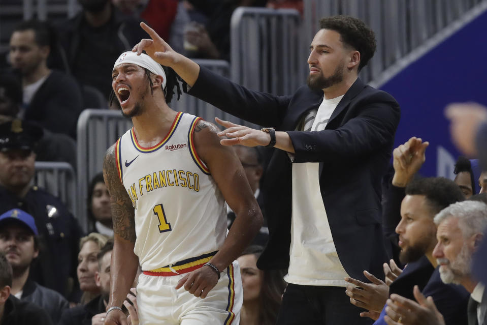 Injured Golden State Warriors guard Klay Thompson, right, and guard Damion Lee (1) react after Alec Burks scored during the first half of the team's NBA basketball game against the Minnesota Timberwolves in San Francisco, Monday, Dec. 23, 2019. (AP Photo/Jeff Chiu)