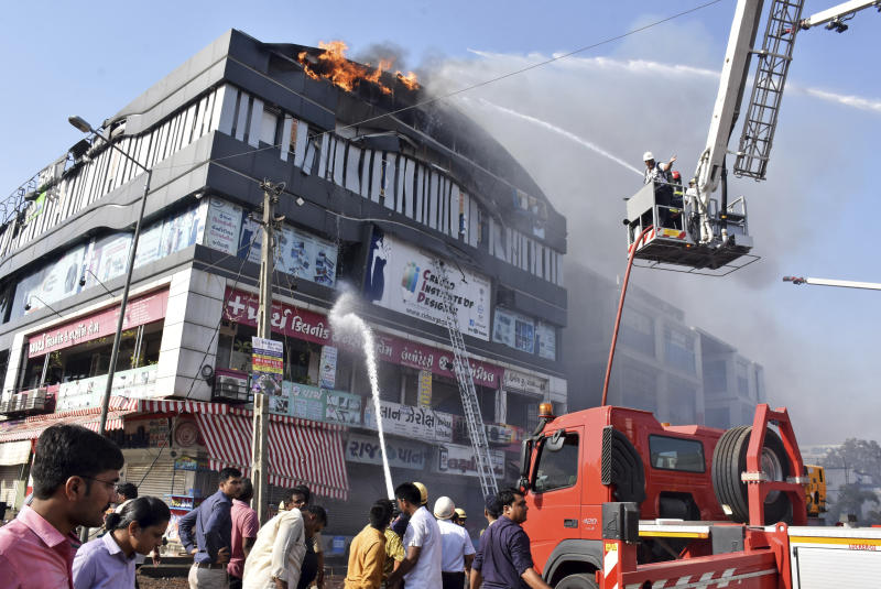 Firefighters work to douse flames on a building in Surat, in the western Indian state of Gujarat, Friday, May 24, 2019. At least 17 teenage students were killed in a fire that broke out Friday in a four-story building, police said. Television images showed some students jumping from the building to escape the blaze with a thick smoke billowing from the building. (AP Photo/Sarju Parekh)