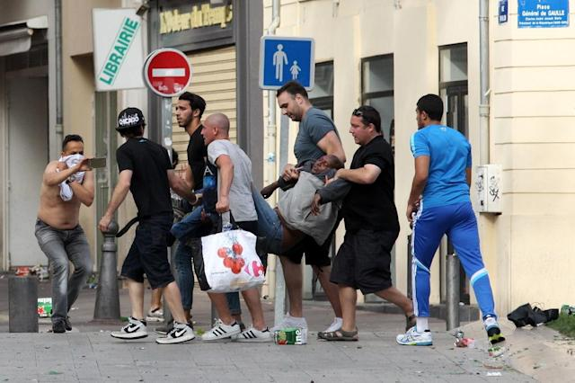 A man injured after a street brawl is carried to a recue squad ahead of the Euro 2016 match England vs Russia, in Marseille, on June 11, 2016 (AFP Photo/Jean Christophe Magnenet)