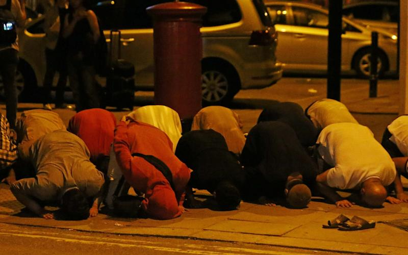 Men pray after a vehicle collided with pedestrians near a mosque in Finsbury Park in north London - Credit: Reuters